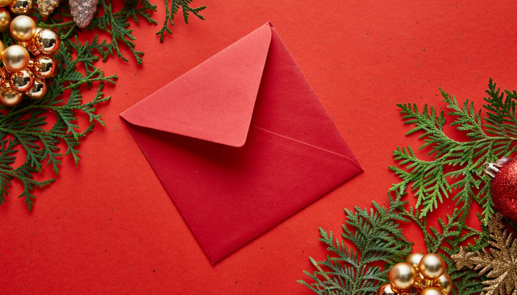 Top View Of Red Envelope Near Shiny Christmas Decoration On Gree